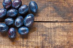 Stock Photo of fresh plums on old wooden table