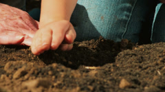 A Grandmother and granddaughter pat soil as they garden together. - stock footage