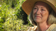Stock Video Footage of Old woman in a straw hat smiles and then returns to working in her garden.