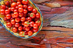 basket of ripe cherry tomatoes on rustic stripped bark - stock photo