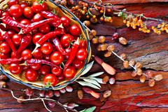 Stock Photo of basket of ripe cherry tomatoes and dried red chillies on rustic stripped bark