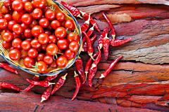 basket of ripe cherry tomatoes and dried red chillies on rustic stripped bark - stock photo