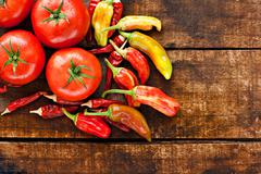 assortment of chilli peppers and tomato on a rustic wooden table - stock photo