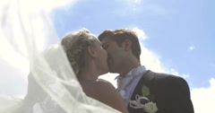 Bride and groom kissing each other outside on a sunny day - stock footage