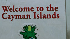 Cayman Islands, welcome sign of cayman islands and pan to the shore street Stock Footage