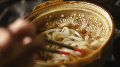 Noodles being cooked is small bowl over flame. Medium shot. Stock Footage
