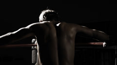A boxer stands in the corner of the ring and prepares to fight in the shadows Stock Footage