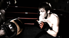 A realistic look at a coach training a mixed martial arts fighter. Medium shot. - stock footage