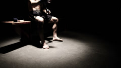 Mixed martial arts athlete sits on a bench and tapes his hands. Wide shot. - stock footage