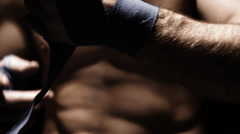 Caucasian athlete methodically wraps his hand with blue cloth. Close up shot. - stock footage