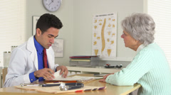 Puerto Rican Doctor taking notes at desk Stock Footage