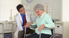 Mexican doctor talking to disabled elderly patient - stock footage