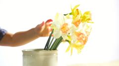 Cute toddlers grabs flowers from a vase and fills her hands - stock footage