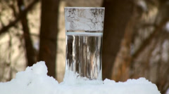 Freezing water in the thin tall glass in time lapse. Stock Footage