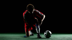 A soccer player kneels down and ties his cleats - stock footage