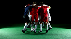A group of soccer players huddle in a circle and jump together in unison - stock footage
