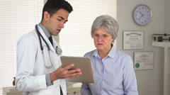 Mexican doctor talking to mature woman with tablet Stock Footage