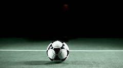 Soccer player kicks ball up into his hands and looks into camera, focused - stock footage