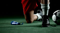 Soccer player puts on shin pads, preparing to play. Close up shot Stock Footage