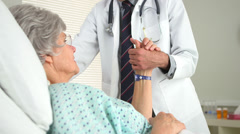 Elderly woman holding her doctor's hand Stock Footage