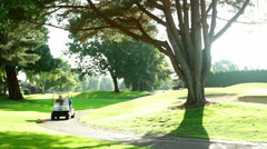 A golf cart comes around the corner on the golf cart path during a sunny day Stock Footage