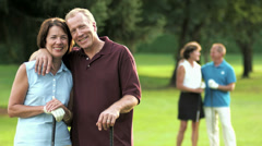 Happy golfing couple smiles into the camera while others talk in the background. Arkistovideo