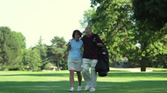 A happy couple walk down the fairway as they talk. Wide shot. Arkistovideo