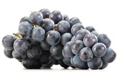 bunch of fresh red grapes isolated on white - stock photo