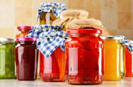 Stock Photo of composition with jars of marinated food. pickled vegetables and jams