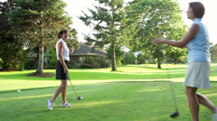 Two female golfers on a tee box greet each other. Wide shot. - stock footage