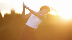 Female golfer tees off in the sunset. Medium shot. Stock Footage
