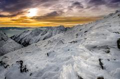 winter mountains with frozen snow and icing at sunset - stock photo