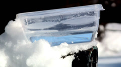 Freezing water in the plastic container Stock Footage