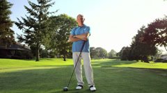 Baby boomer golfer stands with his arms crossed and looks into the camera - stock footage