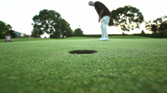 A male golfer sinks a put and gets excited. Wide shot. Stock Footage