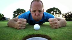 Golfer lays down and tries to blow his ball into the hole. Close up shot. - stock footage