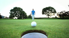 Golfer is upset that his ball won't go into the hole. Close up shot. - stock footage