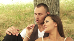 Happy couple spend time together under a tree - stock footage