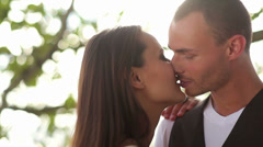 Stock Video Footage of Attractive couple kiss each other then glance into the camera