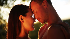 Attractive couple lean their foreheads on one another and kiss Stock Footage