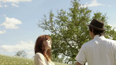 A cute young couple hold hands and dance and play in a sunny open field Stock Footage