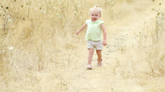 An adorable little girl runs toward the camera with a huge grin on her face - stock footage
