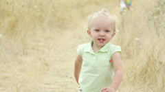 An extremely cute toddler runs toward the camera smiling. Stock Footage