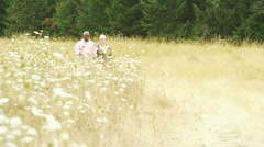 A baby boomer couple take a walk and talk in a field. - stock footage