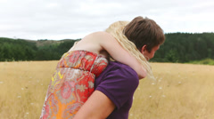 Boyfriend gives girlfriend a piggy back ride and spins. Stock Footage