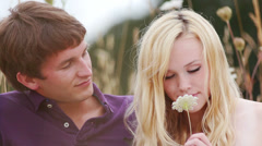 Young couple sit in a field together and smell a flower. - stock footage