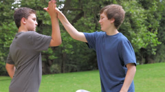 Brothers high five each other then walk away from each other. Medium shot. Stock Footage