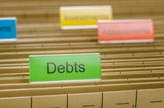 hanging file folder labeled with debts - stock photo