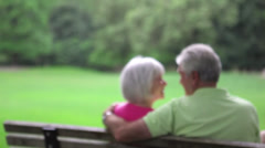 Husband and wife sitting on bench hold each other and kiss. Medium shot. Stock Footage