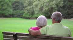 Senior couple sitting on a bench eskimo kiss. Medium shot. - stock footage